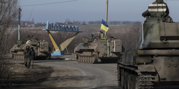 Ukrainian troops ride on armored vehicles towards Artemivsk, eastern Ukraine, Monday, Feb. 23, 2015. A Ukrainian military spokesman says continuing attacks from rebels are delaying Ukrainian forces' pullback of heavy weapons from the front line in the country's east. (AP Photo/Evgeniy Maloletka)