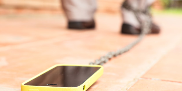 Man walking with smartphone chained to his leg. Conceptual picture for internet addiction.