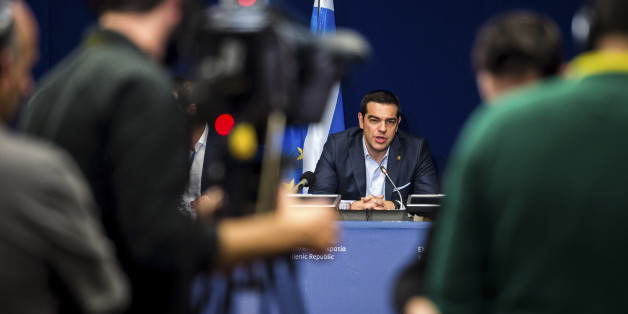 Greek Prime Minister Alexis Tsipras, center, speaks during a media conference after an EU summit in Brussels on Thursday, Feb. 12, 2015. European Union leaders on Thursday said the full respect of the planned weekend cease-fire in eastern Ukraine will be essential before there could be a change in the sanctions regime imposed on Moscow. (AP Photo/Geert Vanden Wijngaert)