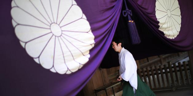 A Shinto priest walks at Yasukuni Shrine during an annual autumn festival in Tokyo, Friday, Oct. 17, 2014. (AP Photo/Eugene Hoshiko).