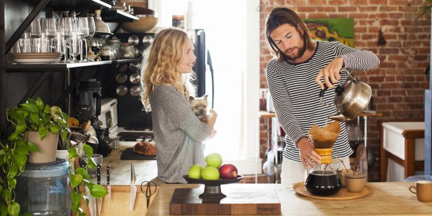 young couple making morning coffee in their kitchen while woman cradles small dog
