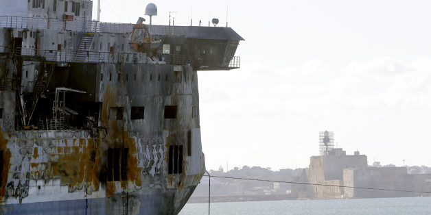 A detail of the Norman Atlantic ferry as it is being towed into the port of Brindisi, Italy, Friday, Jan. 2, 2015. The blaze that broke out Sunday and torched the ferry has killed at least 11 people and authorities prepared to search it for possible more dead. Italy says 477 people were rescued, most by helicopters that plucked survivors off the top deck in gale-force winds and carried them to nearby boats. (AP Photo/Antonio Calanni)