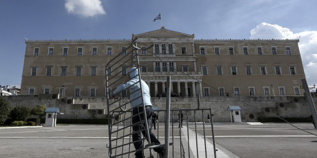 Following instructions from Greece's new left-wing public order minister, a worker removes crowd barriers that since early in the financial crisis screened off the Unknown Soldier's monument in front of Parliament in Athens, Wednesday, Jan. 28, 2015. The spot was a focal point for often violent anti-austerity protests. Greece's radical new government on Wednesday signaled the country would backtrack or scrap a series of budget measures its eurozone creditor nations had demanded in exchange for bailout loans. (AP Photo/InTime News, Kostas Baltas)  GREECE OUT