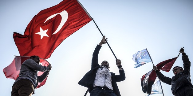 Supporters of Turkey's main opposition Republican People's Party (CHP) wave Turkish and party flags during an election rally at Kadikoy in Istanbul on March 29, 2014. Turkey gears up for local elections on March 30 ahead of a presidential vote in six months and parliamentary polls next year. Turkey's Premier Recep Tayyip Erdogan and his Islamic-leaning party, after over a decade in power, face the first electoral test following months of political turmoil, with mass street protests and a corruption scandal spread via Twitter, Facebook and YouTube. Amid an atmosphere of distrust ahead of tomorow's election with over 50 million eligible voters, the CHP and tens of thousands of citizen volunteers plan to monitor the ballot count. AFP PHOTO / BULENT KILIC        (Photo credit should read BULENT KILIC/AFP/Getty Images)