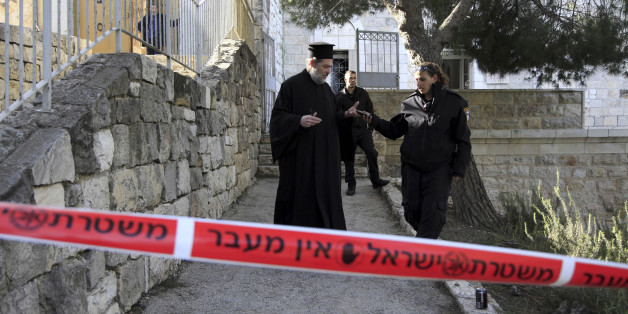 A Greek Orthodox priest talks to Israeli policewoman outside a seminary in Jerusalem, Thursday Feb. 26, 2015. The Greek Orthodox seminary was damaged in fire and anti-Christian slogans were written in Hebrew, in what Israeli police said the suspect was a hate crime. (AP Photo/Mahmoud Illean)