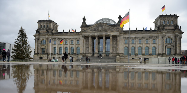 The German parliament building 'Reichstag' is mirrored in a puddle as tourists take pictures, in Berlin, Tuesday Dec. 23, 2014.  (AP Photo/dpa, Rainer Jensen)
