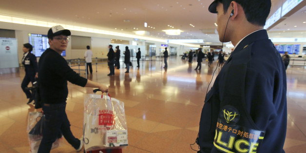 An officer from the anti-terrorism unit of Japan's Metropolitan Police Department keeps guard on the arrival lobby of the international terminal at Haneda Airport in Tokyo Monday, Feb. 2, 2015. Appalled and saddened by news of Japanese hostage Kenji Goto's death following the release of a video showing his killing, purportedly by the Islamic State group, Japan has ordered heightened security precautions at airports and at Japanese facilities overseas, such as embassies and schools. (AP Photo/Koj