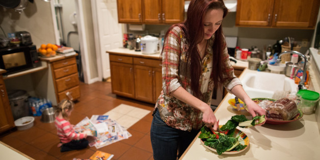 Maggie Barcellano prepares dinner at her father's house in Austin, Texas, on Saturday, Jan. 25, 2014. Barcellano, who lives with her father, enrolled in the food stamps program to help save up for paramedic training while she works as a home health aide and raises her three-year-old daughter. (AP Photo/Tamir Kalifa)
