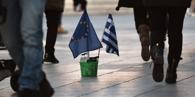 People walk next to a Greek and an EU flag in Athens on February 25, 2015. The hard work for Greece's new anti-austerity government began Wednesday of living up to promises made not only to international creditors but also to voters expecting relief from years of painful cuts. AFP PHOTO / ARIS MESSINIS        (Photo credit should read ARIS MESSINIS/AFP/Getty Images)