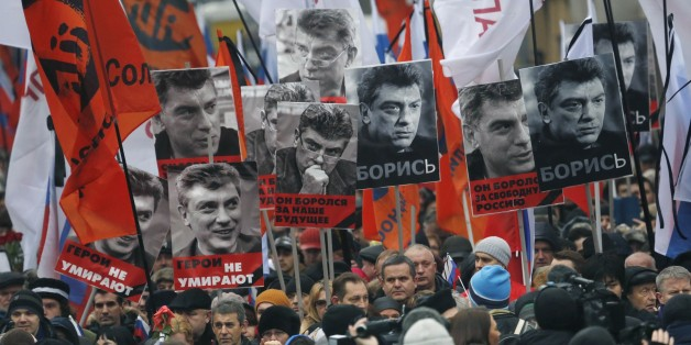People march in memory of opposition leader Boris Nemtsov, who was gunned down on Friday, Feb. 27, 2015, with portraits of him and words read ' he died for the future of Russia, heroes never die!', near the Kremlin in Moscow, Russia, Sunday, March 1, 2015. Russian investigators, politicians and political commentators on state television on Saturday covered much ground in looking for the reason Nemtsov was gunned down in the heart of Moscow, but they sidestepped one possibility, that he was murde