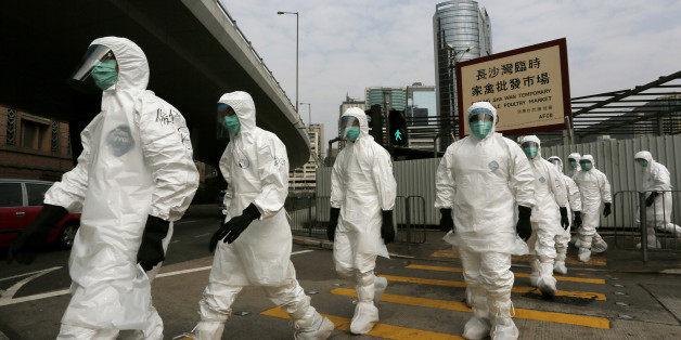 Health workers in full protective gear walk at a wholesale poultry market before culling the poultry in Hong Kong, Tuesday, Jan. 28, 2014. Hong Kong authorities began culling 20,000 birds at a wholesale market after poultry from southern mainland China tested positive for the H7N9 virus, the first time it had been found in imported poultry in Hong Kong. (AP Photo/Vincent Yu)