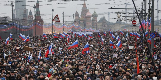 People carry Russian national flags during a march in memory of opposition leader Boris Nemtsov who was gunned down on Friday, Feb. 27, 2015 near the Kremlin, with The Kremlin Wall and St. Basil Cathedral in the background  in Moscow, Russia, Sunday, March 1, 2015. Thousands converged Sunday in central Moscow to mourn veteran liberal politician Boris Nemtsov, whose killing on the streets of the capital has shaken Russia's beleaguered opposition. They carried flowers, portraits and white sig