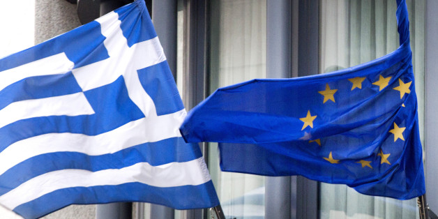 The Greek, left, and EU flag flap in the wind outside the Greek embassy in Brussels on Friday, Feb. 20, 2015. Eurozone finance ministers meet for a crucial day of talks to see whether a Greek debt relief proposal is acceptable to Germany and other nations using the common currency. (AP Photo/Virginia Mayo)