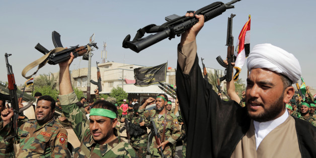 "FILE - In this Saturday, June 21, 2014  file photo, volunteers of the newly formed ""Peace Brigades"" raise their weapons and chant slogans against the al-Qaida-inspired Islamic State of Iraq and the Levant during a parade in the Shiite stronghold of Sadr City, Baghdad, Iraq. When the Islamic State group staged a lightning advance across much of northern Iraq last year, it expanded its rule to about a third of the country, drawing in different groups with different motivations for taking up arms."