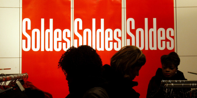 Shoppers look at  clothes next to sales posters during the first day of the winter sales in Paris, Wednesday, Jan. 6, 2010. (AP Photo/Christophe Ena)
