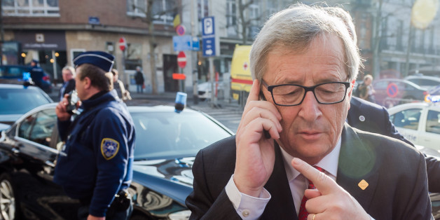European Commission President Jean-Claude Juncker makes a phone call as he arrives for a meeting  ahead of an EU summit in Brussels on Thursday, Feb. 12, 2015. EU leaders meet for a one-day summit on Thursday to discuss, among other issues, European banks and the situation in Ukraine. (AP Photo/Geert Vanden Wijngaert)