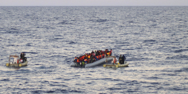 In this file photo taken on Thursday, Dec. 4, 2014 provided by the Italian Navy, rescue crews approach migrants on a rubber boat some 40 miles (65 kilometers) from the Libyan capital, Tripoli. Rescue crews discovered 16 bodies in a migrant boat off Libya, the first reported deaths since the European Union took over Mediterranean rescue operations, the Italian navy said Friday. Migrants dreaming of Europe have their pick of social media sites that work like an online travel agent, advertising fares and offering tips on secure payments. Meanwhile, the traffickers who send them floating across the Mediterranean are buying scrapyard cargo ships over the Internet. (AP Photo/Italian Navy, file)