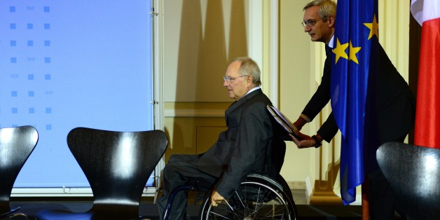 German Finance Minister Wolfgang Schaeuble (L) arrives on his wheelchair pushed by his spokesman Martin Jaeger for a press conference with his French counterpart on December 2, 2014 at the Finance ministry in Berlin following a meeting to discuss how to revive the struggling eurozone.  AFP PHOTO / JOHN MACDOUGALL        (Photo credit should read JOHN MACDOUGALL/AFP/Getty Images)