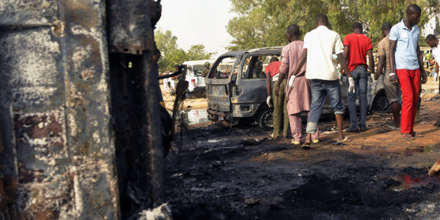 Men inspect the site of a suicide bomb explosion at a bus station in Kano, Nigeria, Tuesday, Feb. 24, 2015. Teenage suicide bombers, suspected to be Boko Haram extremists, killed at least 24 people in separate blasts Tuesday at crowded bus stations in two northern Nigerian cities 300 kilometers (200 miles) apart. (AP Photo/Sani Maikatanga )