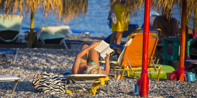 RHODES, GREECE - AUGUST 23: Woman in a bikini is reading and taking a sunbath  at the beach in Gennadi on August 23, 2012 in Rhodes, Greece . Rhodes is the largest of the Greek Dodecanes Islands. (Photo by EyesWideOpen/Getty Images)