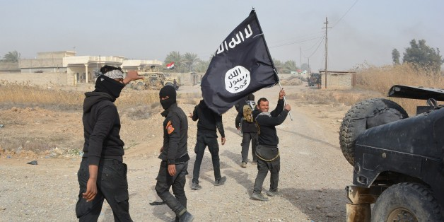 Iraqi government forces celebrate while holding an Islamis Sate (IS) group flag after they claimed they have gained complete control of the Diyala province, northeast of Baghdad, on January 26, 2015 near the town of Muqdadiyah. Iraqi forces have 'liberated' Diyala province from the Islamic State jihadist group, retaking all populated areas of the eastern region, a top army officer said today. The symbolic victory for Baghdad, which has at times struggled to push IS back, could clear the way for further advances against the jihadists . AFP PHOTO / YOUNIS AL-BAYATI        (Photo credit should read YOUNIS AL-BAYATI/AFP/Getty Images)
