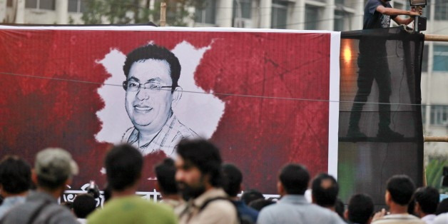 A Bangladeshi activist sets up a light on a poster displaying a portrait of Avijit Roy as others gather during a protest against the Roy in Dhaka, Bangladesh, Friday, Feb. 27, 2015. Roy, a prominent Bangladeshi-American blogger known for speaking out against religious extremism was hacked to death as he walked through Bangladesh's capital with his wife, police said Friday. (AP Photo/A.M. Ahad)