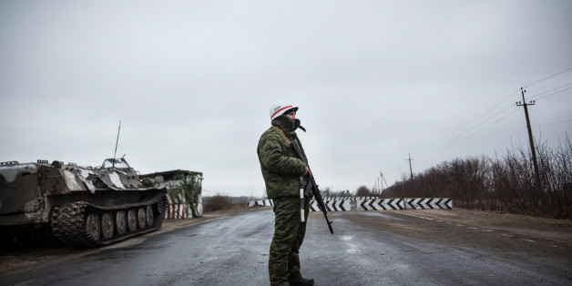 NOVOAZOVSK, UKRAINE - MARCH 04:  A pro-Russian seperatist stands guard at a check point on the road heading to Mariupol on March 4, 2015 in Novoazovsk, Ukraine. Novoazovsk lies east of the port city of Mariupol, which many believe pro-Russian rebels may try to take control of next, in an effort to create a land bridge between the Russian annexed peninsula of Crimea and mainland Russia.  (Photo by Andrew Burton/Getty Images)
