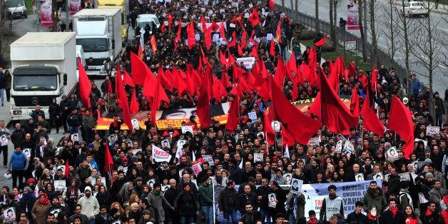 Demostrators march with red flags and posters of Berkin Elvan in Istanbul on March 7, 2015, as thousands of people marched to mark the first anniversary of the death of the youngest victim of the Gezi Park protests. Berkin Elvan was 14-years-old when he was hit by a police teargas canister in Istanbul on June 16, 2013, as anti-government demonstrations swept Turkey. AFP PHOTO/OZAN KOSE        (Photo credit should read OZAN KOSE/AFP/Getty Images)