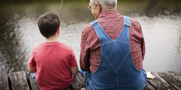 Color image of a young boy fishing with his grandfather while sitting on a dock.