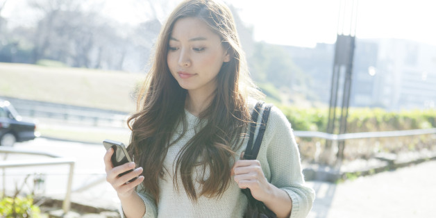 Young woman using smartphone on street