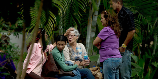 Josefa Alvarez de Gonzalez, center, is comforted by relatives of her husband, Rodolfo Gonzalez, outside the morgue office in Caracas, Venezuela, Friday, March 13, 2015. Rodolfo Gonzalez  who was arrested last year during demonstrations against the Venezuela's President Nicolas Maduro government has died in state custody. The family of Gonzalez said that he died while being held at the headquarters of Venezuela's intelligence police. The 64-year-old pilot had been jailed since April 2014 and was