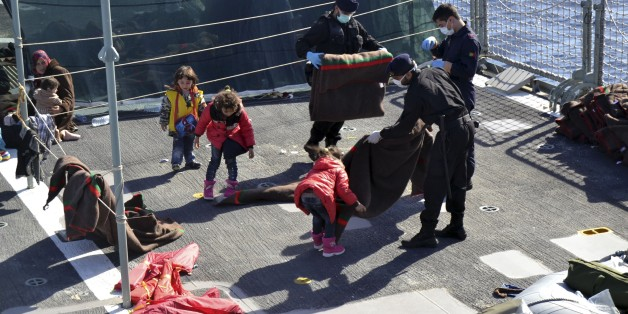 In this photo taken on Saturday, Nov. 15, 2014 and provided by the Portoguese Navy, sailors and children fold blankets on the dock of the Portoguese Navy vessel Viana do Castelo. The Portuguese open sea patrol vessel the Viana Do Castelo made its first rescue of migrants as part of Operation Triton, the EU operation that has stepped in to help Italy patrol its coastline. A spokeswoman for Frontex, the European Agency that coordinates Triton deployment, told the Associated Press that in recent days Operation Triton has rescued over 600 migrants. The European Operation Triton is taking over from the Italian Operation Mare Nostrum which was launched by the Italian government in October of 2013, following a migrant shipwreck that left over 300 people dead just off the coast of Lampedusa, the small strip of island that is part of Italy but closer to the African mainland. (AP Photo/Portuguese Navy, ho)