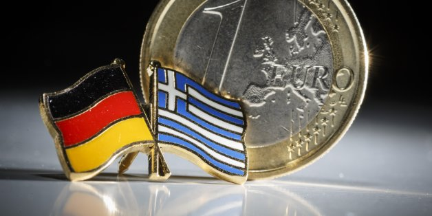 BERLIN, GERMANY - FEBRUARY 10: Symbolic photo of Greece and the Euro, one euro coin behind a badge with the national flags of Greece and Germany on February 10, 2015 in Berlin, Germany.  (Photo by Thomas Trutschel/Photothek via Getty Images)