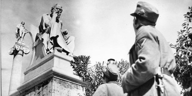 German troopers in their field grey uniforms look up at two ancient Greek statues on the Acropolis in Athens, Greece on June 15, 1941 during World War II.  The statue in front is of Greek philosopher Socrates.  (AP Photo)