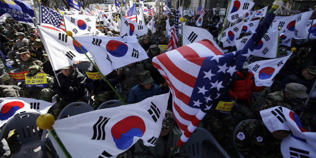 South Korean Vietnam War veterans hold flags from South Korea and the United States during a rally denouncing the attack on U.S. Ambassador to South Korea Mark Lippert in downtown Seoul, South Korea, Monday, March 9, 2015. South Korea's president visited injured U.S. Ambassador Mark Lippert on Monday amid an outpouring of public sympathy and support for the envoy who is recovering from an attack by a knife-wielding man. (AP Photo/Lee Jin-man)