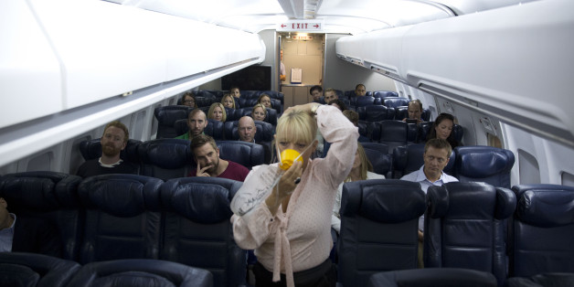 In this Sept. 10, 2014 photo, British Airways flight safety instructor Diane Pashley demonstrates the use of an oxygen mask during a British Airways Flight Safety training course at the airline's Cranebank training facility, near Heathrow airport in London. The half-day safety course, open to frequent fliers willing to pay $265, encourages passengers to be aware of their surroundings and familiarize themselves with what happens in an emergency. (AP Photo/Matt Dunham)