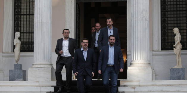 Greece's Prime Minister Alexis Tsipras, center, accompanied by close associates, walks out of his office on his way to the Presidential Palace to attend his government's swearing in ceremony in central Athens, Tuesday, Jan. 27, 2015. Tsipras picked an outspoken bailout critic, Yanis Varoufakis, as his new finance minister Tuesday, signaling his revolve to take a tough line with eurozone lenders in an effort to write off a massive chunk rescue debt. (AP Photo/Lefteris Pitarakis)