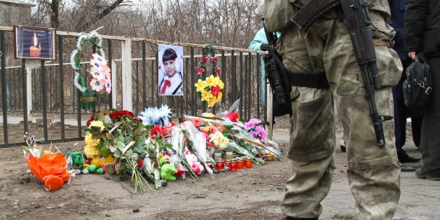A Ukrainian soldier stands near the place where a Ukrainian armored vehicle ran over a family, killing an 8-year old girl, in Kostyantynivka, Ukraine, Tuesday, March 17, 2015. Residents in the eastern Ukrainian town of Kostyantynivka angrily confronted police officials Tuesday over the accident in which an armored military vehicle struck and killed an 8-year old girl, prompting clashes in front of a dormitory that has been commandeered by soldiers engaged in combat against Russian-backed separat