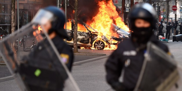 Riot Police form a cordon as a Police car burns on the opening day of the European Central Bank (ECB) in Frankfurt am Main, western Germany, on March 18, 2015. Supporters of the so-called Blockupy alliance consisting of social movements, activists, workers, trade unions and parties are expected to stage large protests against austerity and the authority of the European Central Bank when the bank's new headquarters officially will be on March 18, 2015.      AFP PHOTO / ODD ANDERSEN        (Photo
