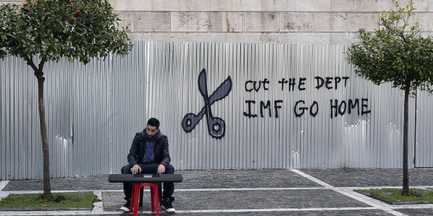 A man plays music on a digital keyboard near graffiti on a corrugated metal gate reading 'Cut the debt, IMF go home' in Athens on February 24, 2015. Greece edged closer to eurozone survival on February 24 as its international creditors and hold-out Germany looked ready to approve the reforms they had demanded of Athens in return for extending its bailout programme. AFP PHOTO / LOUISA GOULIAMAKI        (Photo credit should read LOUISA GOULIAMAKI/AFP/Getty Images)