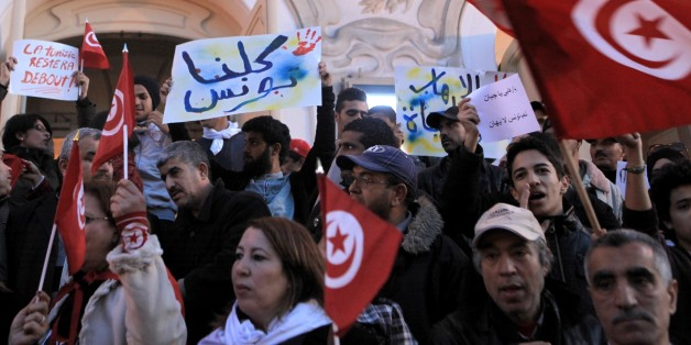 TUNIS, TUNISIA - MARCH 18: A group of people hold banners and shout slogans during a protest against a terrorist gunmen attack at the Bardo Museum, on March 18, 2015 in front of the Tunisian National Theater in Tunis, Tunisia. Terrorist gunmen opened fire at the Bardo Museum in Tunisia's capital, killing 21 people including 2 gunmen and at least 22 people wounded including tourists, the Tunisian Prime Minister said. (Photo by Yassine Gaidi/Anadolu Agency/Getty Images)