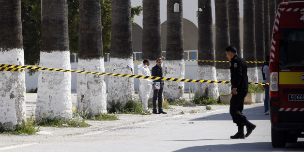 Police officers look for evidence, outside the Bardo museum  in Tunis, Tunisia, Thursday, March 19, 2015, a day after gunmen opened fire killing over 20 people, mainly tourists.  One of the two gunmen who killed 19 tourists and others at a prominent Tunisian museum was known to intelligence services, Tunisia's prime minister said Thursday. But no formal links to a particular terrorist group have been established in an attack that threatens the country's fledgling democracy and struggling tourism industry. (AP Photo/Christophe Ena)