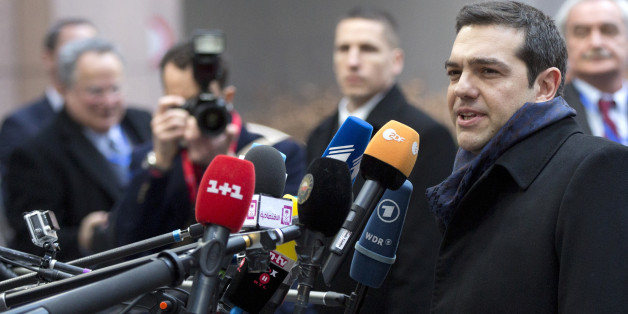 Greek Prime Minister Alexis Tsipras, second right, speaks with the media as he arrives for an EU summit in Brussels on Thursday, Feb. 12, 2015. European Union leaders on Thursday said the full respect of the planned weekend cease-fire in eastern Ukraine will be essential before there could be a change in the sanctions regime imposed on Moscow. (AP Photo/Virginia Mayo)