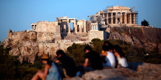 Tourists sit on rocks with a view of the Parthenon temple on Acropolis Hill in Athens, Greece, on Tuesday, Aug. 20, 2013. A third aid program for Greece announced by German Finance Minister Wolfgang Schaeuble yesterday will be partially financed through the EU budget. Photographer: Angelos Tzortzinis/Bloomberg via Getty Images
