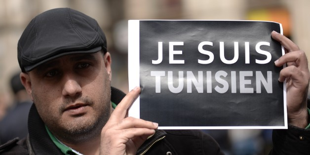 A Tunisan holds up a sign reading, ' I am Tunisian',  during a minute of silence held outside Barcelona's city hall in Barcelona on March 19, 2015 for Spanish victims of a gunmen attack at the Bardo National Museum in the Tunisian capital Tunis that left 21 dead. Nine people suspected of links with the gunmen who attacked the museum have been arrested, the presidency announced today.   AFP PHOTO / JOSEP LAGO        (Photo credit should read JOSEP LAGO/AFP/Getty Images)