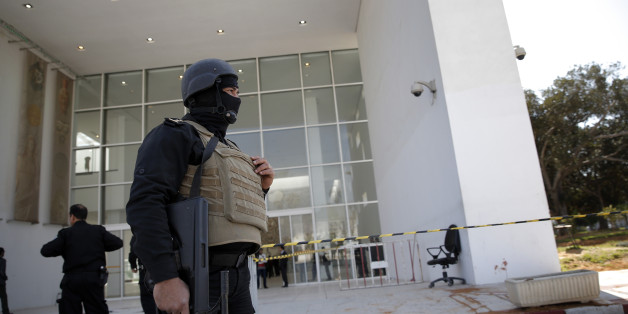 Policemen guard the entrance of the Bardo museum in Tunis, Tunisia, Thursday, March 19, 2015, as a a blood stain is seen at right,  a day after gunmen opened fire killing over 20 people, mainly tourists. One of the two gunmen who killed tourists and others at a prominent Tunisian museum was known to intelligence services, Tunisia's prime minister said Thursday. But no formal links to a particular terrorist group have been established in an attack that threatens the country's fledgling democracy and struggling tourism industry. (AP Photo/Christophe Ena)