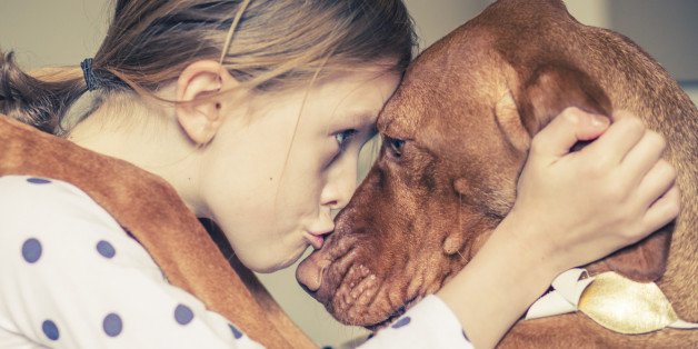 A hug between a young girl and her pet dog.