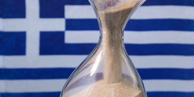 GERMANY, BONN - MARCH 17: Sand glass and a Greek flag.Our picture shows a running sand glass and the Greek flag. (Photo by Ulrich Baumgarrten via Getty Images)