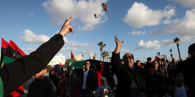 Libyan man throws candies to the people at Tahrir Square, during the second anniversary of the uprising that toppled longtime dictator Moammar Gadhafi in Benghazi, Libya, Sunday, Feb, 17, 2013.  (AP Photo/Mohammad Hannon)