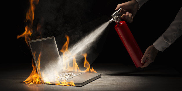 Businessman using fire extinguisher on laptop computer that is in flames